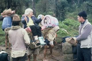 Olga in basket with sherpas helping