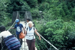 Olga Murray crossing a bridge in the Himalaya
